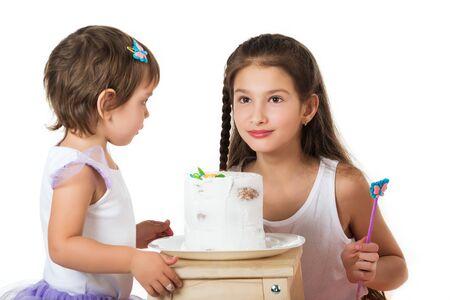 Photo pour Two little girls near the cake on white - image libre de droit