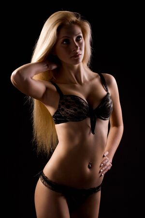Photo for Young slim beautiful blond woman with long hair in sexy black lingerie standing over dark background. Beauty of womans body and sexy underwear concept - Royalty Free Image
