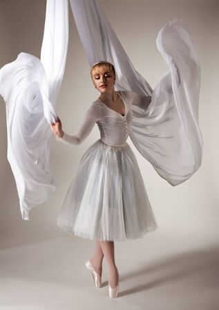 Photo pour Young beautiful blond ballerina woman in white tutu, gloves, jewelry and pointe shoes dancing with white cloth over grey background. Ballet, grace, beauty, art concept - image libre de droit
