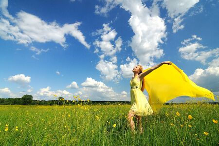 Photo pour A girl in a yellow dress poses with hands up in a green field with a silk cloth in her hands. Beautiful outdoor photo - image libre de droit