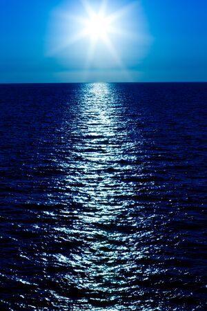 Photo pour Seascape of still sea surface, golden sun in sky on summer clear day. Still landscapes of travels and destination scenics - image libre de droit