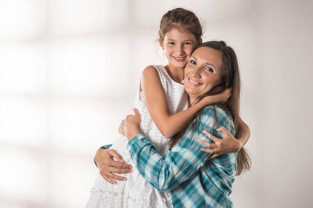 Foto de Young mother hugs her pretty positive daughter - Imagen libre de derechos