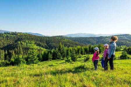 Photo pour Young mother and two little daughters travelers stand on a slope with a gorgeous view of the hills covered with dense fir forest against the blue sky on sunny warm summer day. Family tourism concept - image libre de droit
