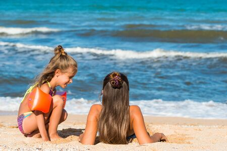 Photo pour Little cheerful girl bury her older sister in sand - image libre de droit