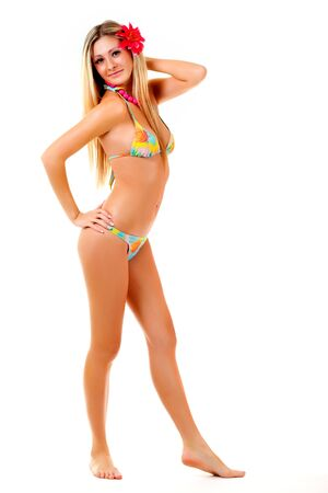 Photo pour Beautiful young cheerful girl in a swimsuit with a red flower in her hair posing on a white background. Concept of body shaping before the beach season. Sea vacation concept. Places for advertising - image libre de droit