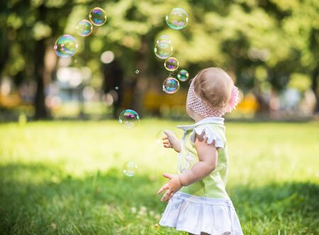 Photo pour Small baby girl walking on grass and trying to catch bubbles - image libre de droit