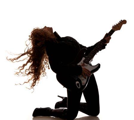 Photo pour Woman squatting and clutching guitar - image libre de droit