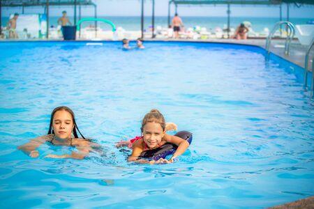 Photo pour Two little sisters girls are swimming - image libre de droit