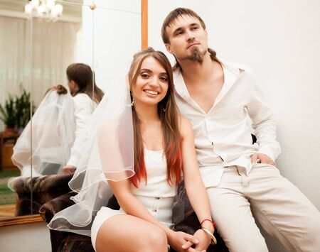 Photo pour Beautiful newlyweds sitting in armchair. - image libre de droit