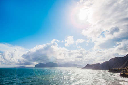 Photo pour Sandy beach with mountains on background. Mountains are covered with grass, and has sheer cliffs from sea. Sky is cloudy - image libre de droit