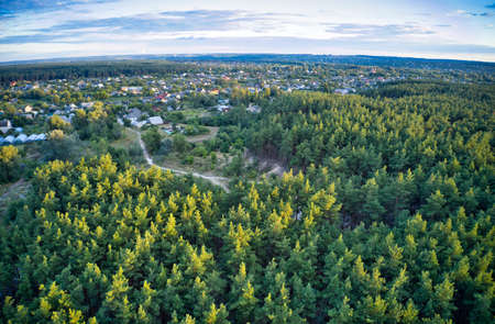 Photo for A beautiful large village around which is a large green spruce forest - Royalty Free Image