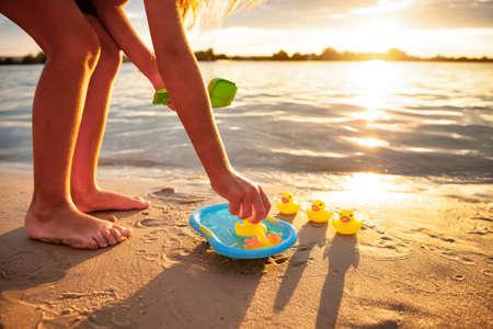 Photo pour Unrecognizable kid playing with rubber duck toys on beach. - image libre de droit