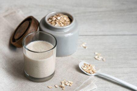 Photo pour Vegan oat milk and ingredients on rustic fabric - image libre de droit
