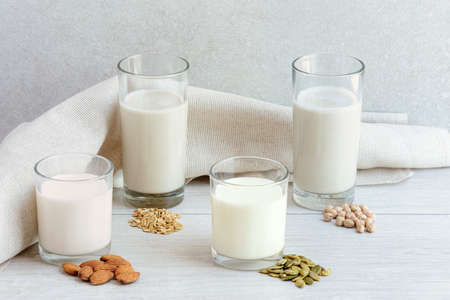 Photo pour Four different glasses of vegan non dairy milk from nuts, seeds, cereals and legumes. Assortment of organic vegan milk - image libre de droit