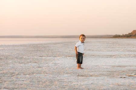 Photo pour Adorable mixed race baby boy portrait. Cute one year old boy playing on the beach of the estuary. Outdoors portrait - image libre de droit