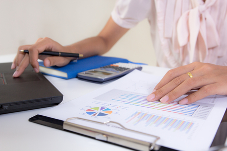 Close up accountant or banker making calculations. Savings,Concept finances and economy,Business women reviewing data in financial statement. Accounting , Accountancy, Bookkeeping Concept