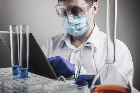 Photo pour Professional scientist holding a test tube and tablet while making a research - image libre de droit