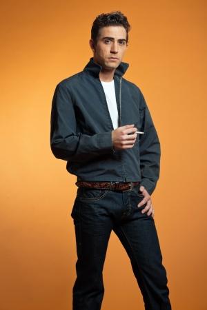 Retro fifties fashion man smoking cigarette. Studio shot. Orange background.