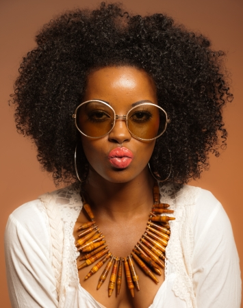 Retro 70s fashion black woman with sunglasses and white shirt. Brown background.