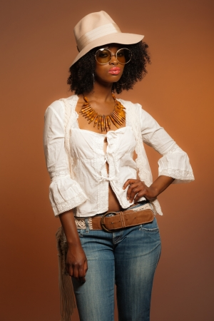 Retro 70s fashion afro woman with sunglasses and white hat. Brown background.