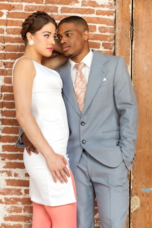 Vintage fashion romantic wedding couple in old urban building. Mixed race.