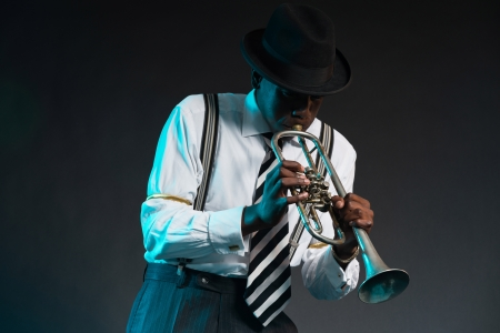 Retro african american jazz musician playing on his trumpet. Wearing shirt and tie and hat. Studio shot.
