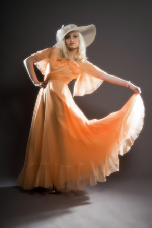 Soft focus retro hippie 70s fashion sensual girl with long blonde hair wearing an orange dress and hat. Studio shot against grey.