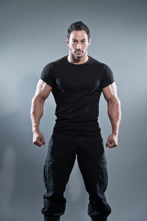 Combat muscled fitness man wearing black shirt and pants. Studio shot against grey.