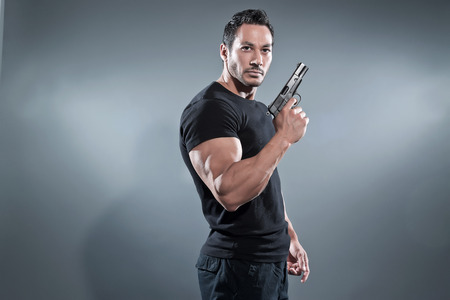 Action hero muscled man holding a gun. Wearing black t-shirt and pants. Studio shot against grey.の写真素材