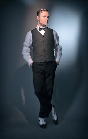 Retro classic business fashion man wearing grey gilet and bow tie. Studio shot.