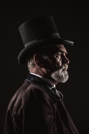 Vintage victorian man with black hat and gray hair and beard. Studio shot against dark background.