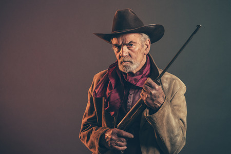 Old rough western cowboy with gray beard and brown hat holding rifle. Low key studio shot.の写真素材