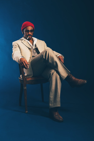 Stylish attractive African American businessman sitting smoking in a chair with a cigarette dangling from his mouth staring absentmindedly at the floor, on blue