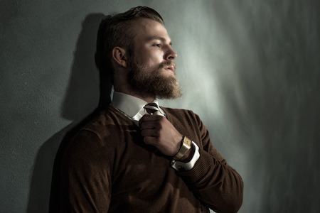 Thoughtful handsome bearded man standing daydreaming with his eyes closed and gripping his necktie, head and shoulders profile view