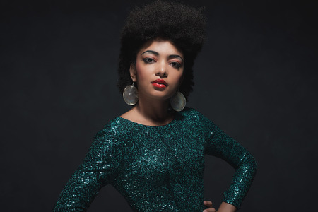 Half Body Shot of an Elegant Young Woman Posing in Sparkling Green Dress with Hands on Waist and Looking at the Camera Against Black Wall Background Inside the Studio.