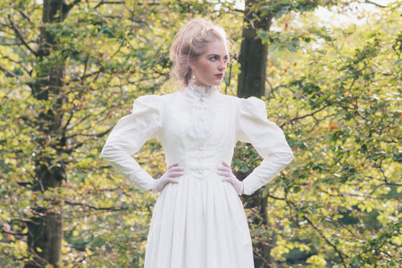 Retro victorian fashion woman in front of trees.