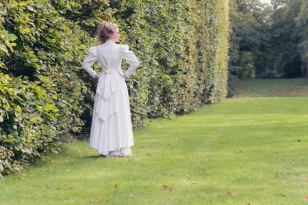 Vintage victorian woman walking in garden looking over shoulder.