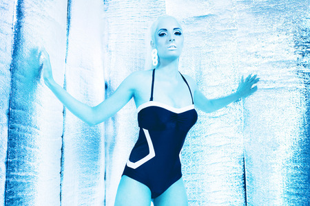 Futuristic swimwear girl standing in silver reflective room.の写真素材