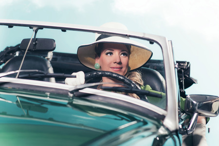 Smiling retro 60s woman with driving sports car.