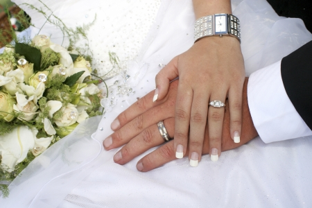 Loving couple holding hands with rings against wedding dressの写真素材