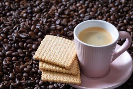 Photo pour Cup of hot espresso coffee and biscuits on coffee beans dark background. - image libre de droit