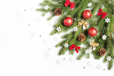 Photo for Christmas tree branch Decorated with cones, snowflakes, bows and red balls with a gold pattern. On white background - Royalty Free Image