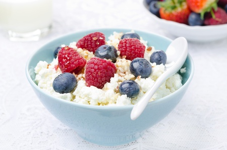 cottage cheese with berries, honey and nuts, fresh berries and milk for breakfast closeup