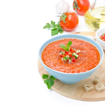 cold tomato soup gazpacho with basil and croutons in a bowl, isolated on a white