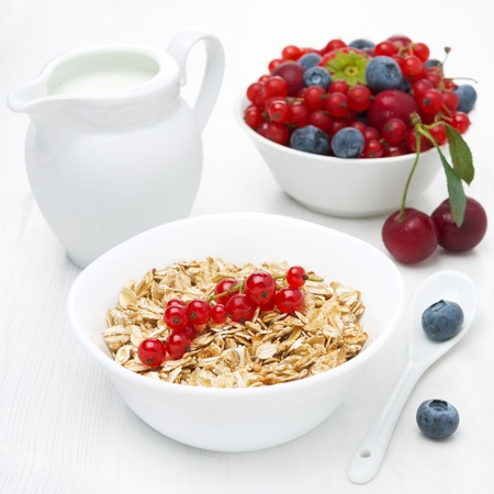 muesli with red currant, bowl of fresh berries and jug of milk for breakfast, close-up