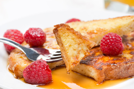 French toast with raspberries and maple syrup, close-up