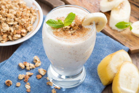 milkshake with banana, granola and cinnamon in a glass, top view, horizontal