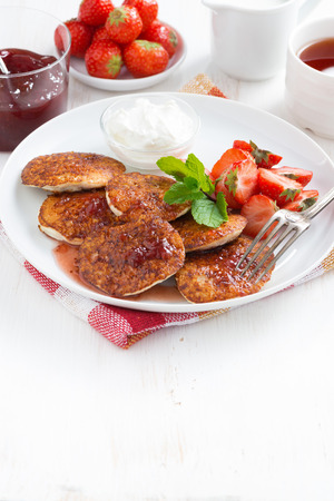 Pancakes with fresh strawberries, jam and tea. White wooden background for text, vertical, top view