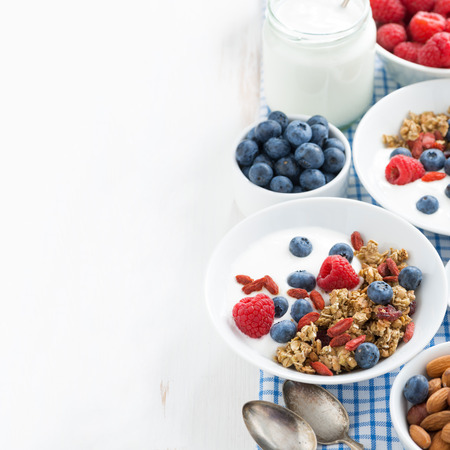 breakfast with granola, yogurt and berries on a white wooden table and space for text, top view