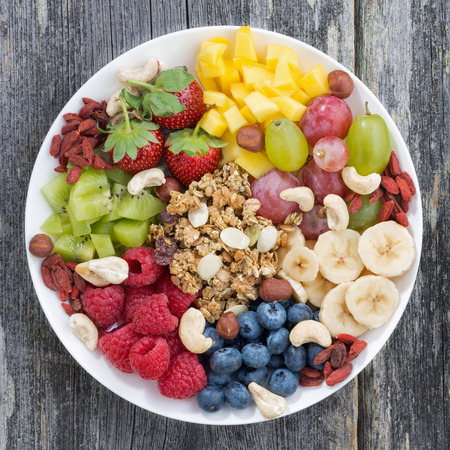 berries, fruits, nuts and granola, products for a healthy breakfast, top view, close-up